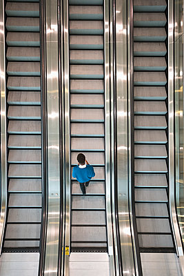 Mixed race businessman riding escalator - p555m1311694 by Jetta Productions
