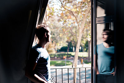 Spiegelung eines jungen Manns im Fenster - p795m2063214 von Janklein