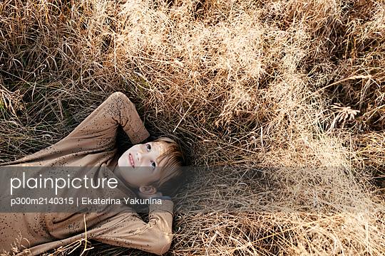 Portrait of smiling boy lying on autumnal meadow - p300m2140315 by Ekaterina Yakunina