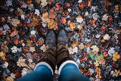 Low section of woman wearing boots while standing on fallen maple leaves during autumn - p1166m1512828 by Cavan Images