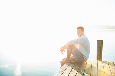 Portrait of smiling young man sitting on jetty at lake by sunrise - p300m2198888 by Daniel Ingold