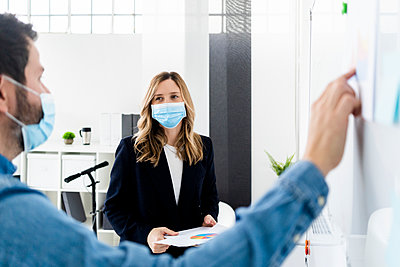 Business people wearing protective masks working in office  - p300m2242559 by Giorgio Fochesato