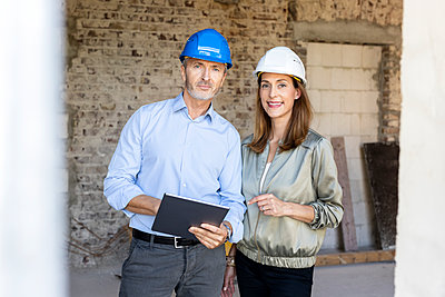 Male architect with digital tablet standing by female client at construction site - p300m2276161 by Peter Scholl