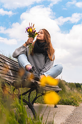 Young woman smelling flowers on bench in nature - p300m2281985 by Josu Acosta