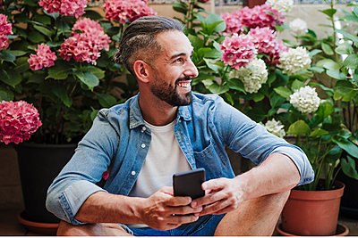 Smiling male freelancer with mobile phone looking away while sitting in front of hydrangea plants - p300m2293386 by Eva Blanco