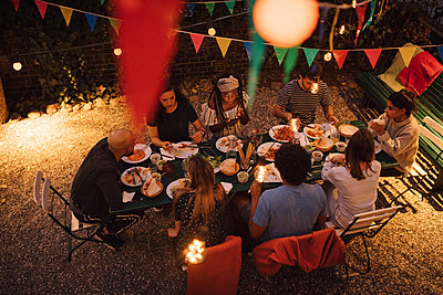 High angle view of multi-ethnic friends having dinner during garden party in backyard - p426m2046191 by Maskot