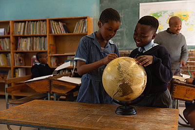 Schoolkids looking at globe in classroom - p1315m2055971 by Wavebreak