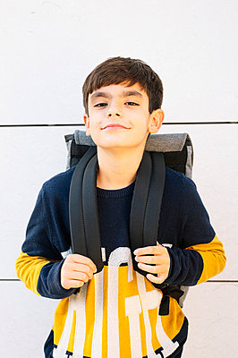 Boy standing with backpack against wall on sunny day - p300m2225889 by Jose Luis CARRASCOSA