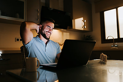 Smiling businessman with hands behind head while working on laptop at dining table at home - p300m2256936 by Miguel Frias