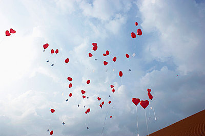 Many red heart shaped helium balloons floating up - p301m744379f by Britta Wendland