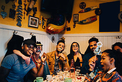 Portrait of cheerful young multi-ethnic friends holding props while sitting at restaurant during dinner party - p426m2046279 by Maskot