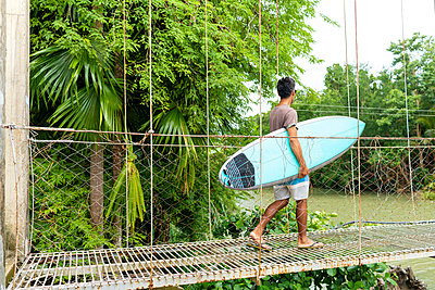 Man with surfboard on rope bridge, Pagudpud, Ilocos Norte, Philippines - p429m2075451 by dotdotred