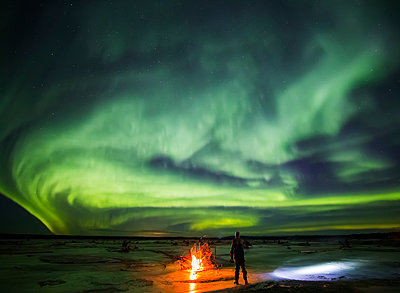Man stands next to a campfire while northern lights dance overhead, Delta River, Delta Junction, Interior Alaska, USA - p442m1225072 by Steven Miley