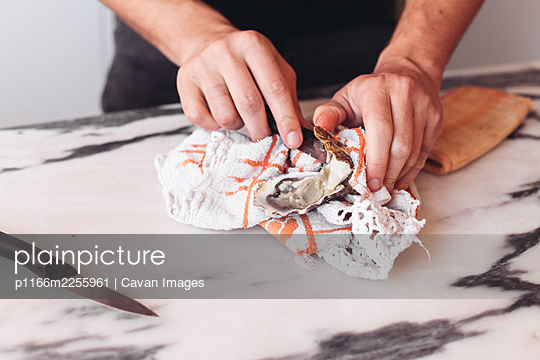 Man opening an oyster with a knife and a towel, marble table - p1166m2255961 by Cavan Images