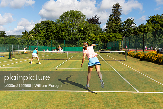 Mature women during a tennis match on grass court - p300m2132598 by William Perugini