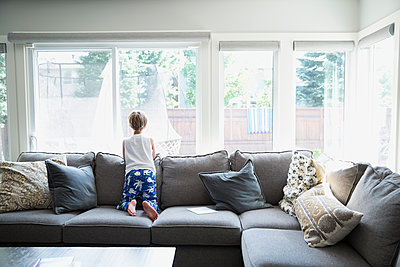 Curious boy in pajamas on sofa looking out living room window - p1192m1184047 by Hero Images