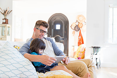 Father and toddler daughter using digital tablet on living room sofa - p1192m1490748 by Hero Images