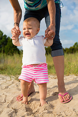 Mid adult woman holding baby daughters hands while toddling in sand - p1427m2283204 by Roberto Westbrook