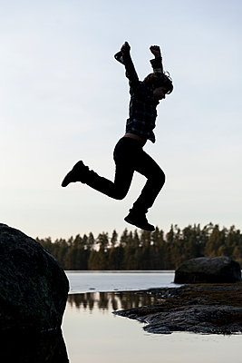 Boy jumping from rock at lake, silhouette - p1687m2295164 by Katja Kircher