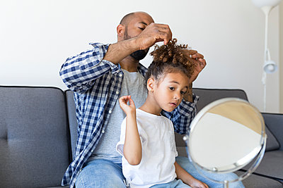 Father doing daughter's hair on couch at home - p300m2114513 von Sus Pons