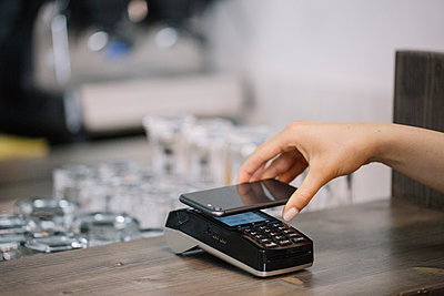 Customer paying cashless with smartphone in a cafe - p300m2140097 by Alberto Bogo