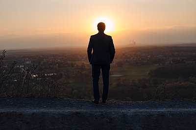 Mature businessman standing on a disused mine tip at sunset looking at view - p300m2189051 by Joseffson