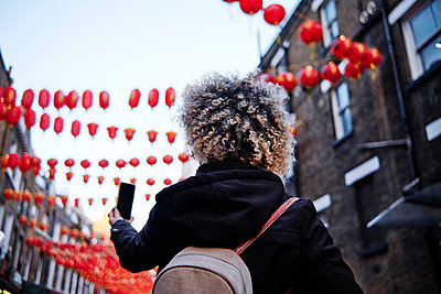 Curly haired woman taking selfie through mobile phone at Chinatown - p300m2273652 by Angel Santana Garcia