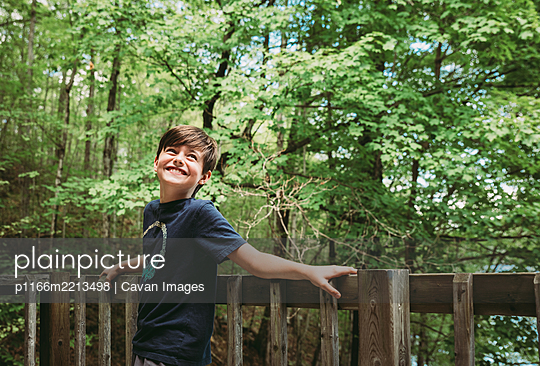 Happy young boy leaning against deck railing with trees in background. - p1166m2213498 by Cavan Images