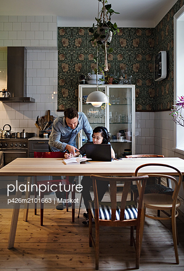 Father assisting son in studying on table at home - p426m2101663 by Maskot