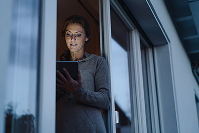 Woman standing in balcony door, using digital tablet - p300m2156314 by Joseffson