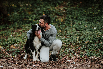 Mature man kissing his dog while sitting at park - p300m2225759 by Gala Martínez López