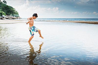 Mixed race boy playing in water on beach - p555m1420071 by Sollina Images