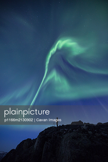 Person with a camera on rocky cliff under the Aurora Borealis  - p1166m2130902 by Cavan Images