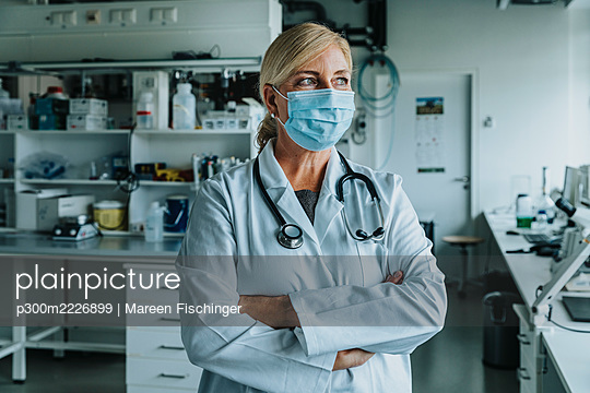Female scientist wearing face mask standing with arms crossed at laboratory - p300m2226899 by Mareen Fischinger