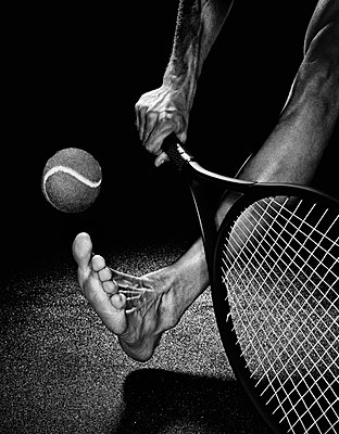 Tennis player with bare feet - p1072m905371 by Michael Steel