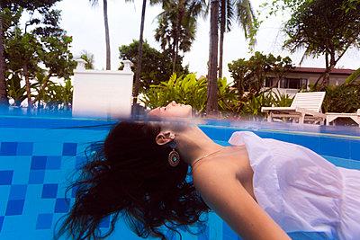 Frau im weißen Kleid treibt im Swimmingpool - p1108m1194357 von trubavin
