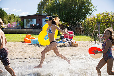 Brother and sisters running and splashing in sunny summer lake - p1192m1183787 by Hero Images