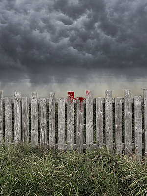 Wooden picket fence with blood stains under a stormy sky - p1280m2278666 by Dave Wall