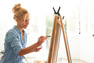 Smiling mature woman painting on paint board at home - p300m2227090 by Pete Muller