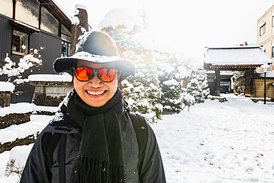 Woman in orange sunglasses and snow covered felt hat in winter, portrait, Takayama, Gifu, Japan - p429m2075043 by Henn Photography