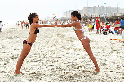 Mixed race friends playing on beach - p555m1479601 by Granger Wootz
