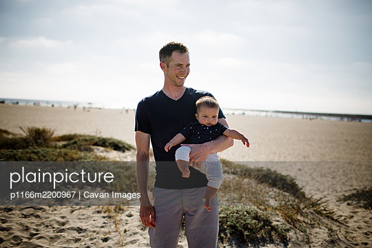 Father Casually Standing on Beach Holding Infant Son - p1166m2200967 by Cavan Images