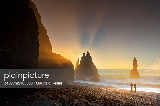 Iceland, South Iceland, Su_urland, Vik i Myrdal, Tourists walking on the volcanic beach in Vik I Myrdal with the sun rising beyond the sea stacks - p1377m2105599 by Maurizio Rellini