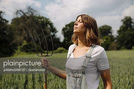 Young woman with hay fork standing in a grain field in the countryside - p300m2206727 by Gustafsson