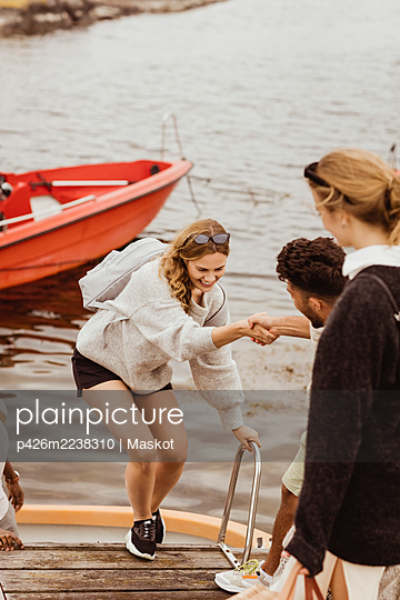 Man helping smiling female friend to climb on jetty - p426m2238310 by Maskot