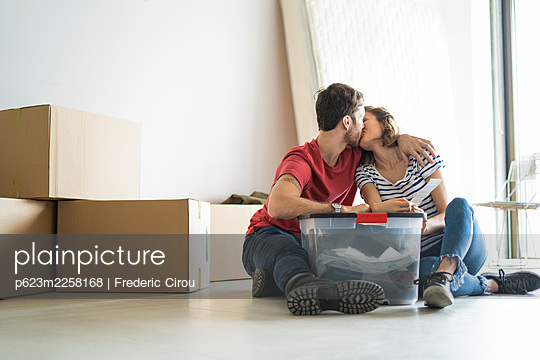 Young couple kissing in their new house - p623m2258168 by Frederic Cirou