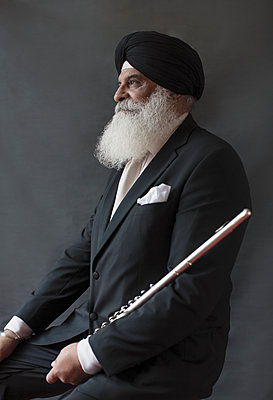 Portrait serious, well-dressed senior man in turban holding flute - p1023m2033399 by Sam Edwards