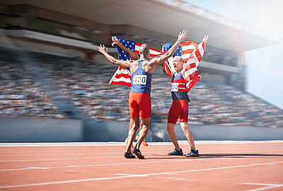 Runners celebrating and holding American flags on track - p1023m923640f by Paul Bradbury