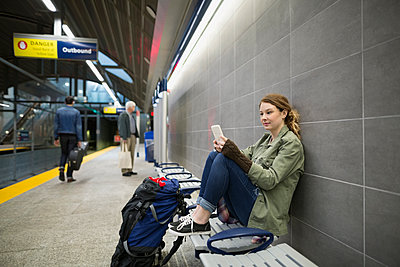Young woman cell phone bench subway station platform - p1192m1129697f by Hero Images