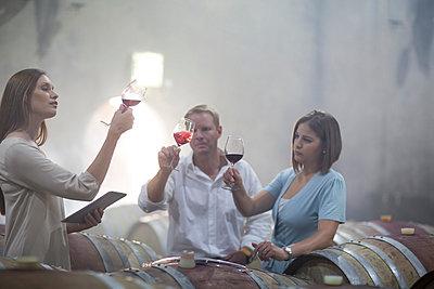 Three people tasting wine in cellar - p300m1028612f by zerocreatives